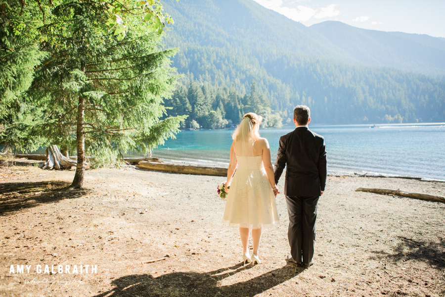 bride and groom standing next to lake in the sunshine