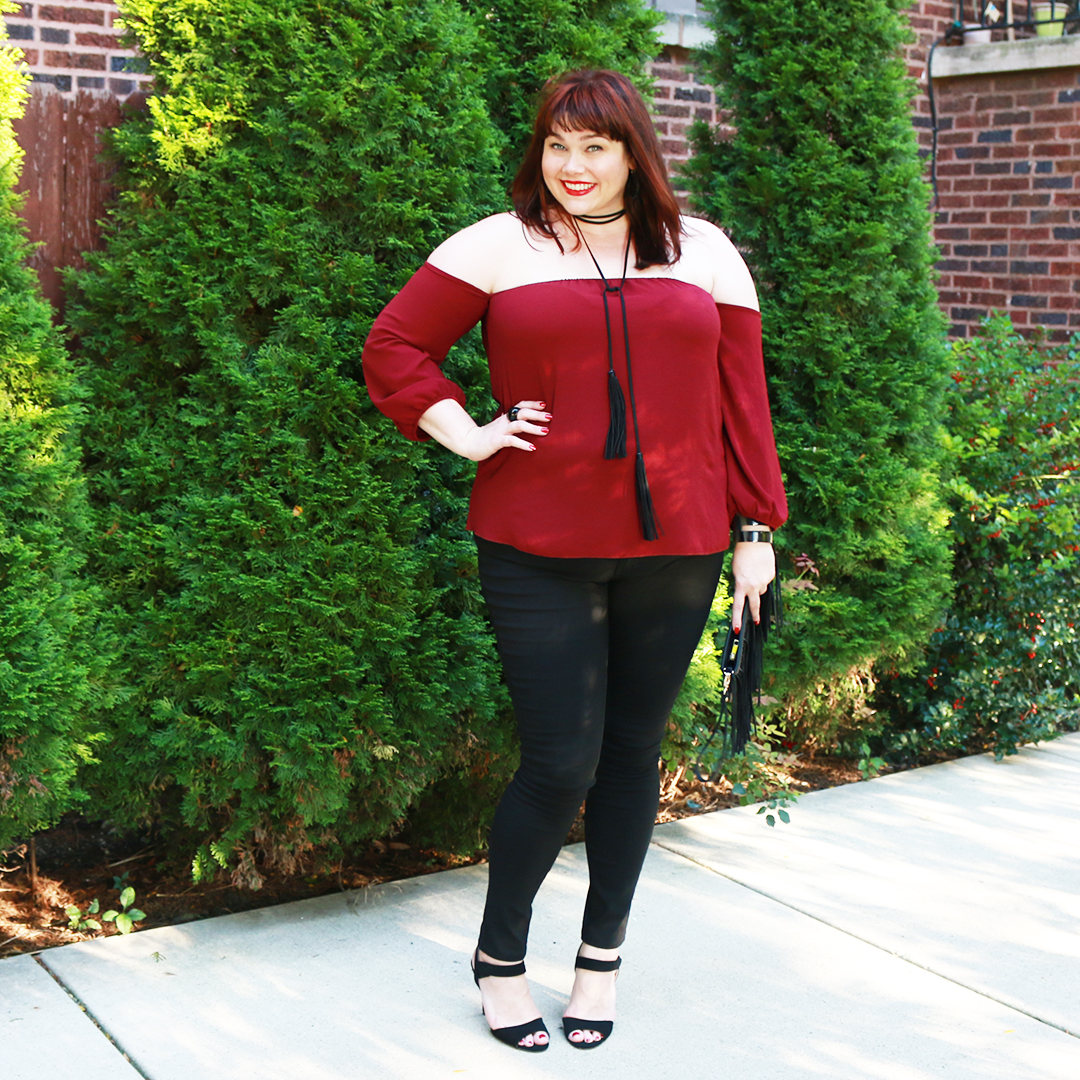 Chicago Plus Size Blogger Amber from Style Plus Curves in Plus Size Off Shoulder Long Sleeve Blouse in Burgundy with Black Plus Size Skinny Jeans and a tassel necklace