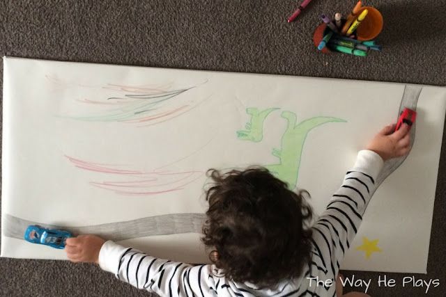 Toddler playing with cars over his drawing