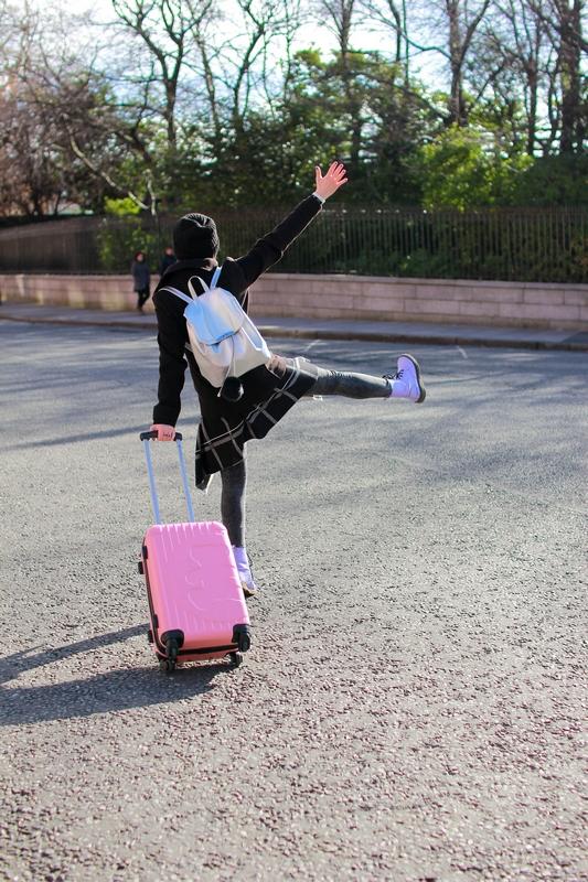 position un peu étrange au milieu de la route avec une valise rose lulu castaniette