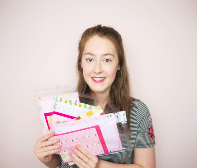 I'm smiling and holding a selection of my prints and letter sets