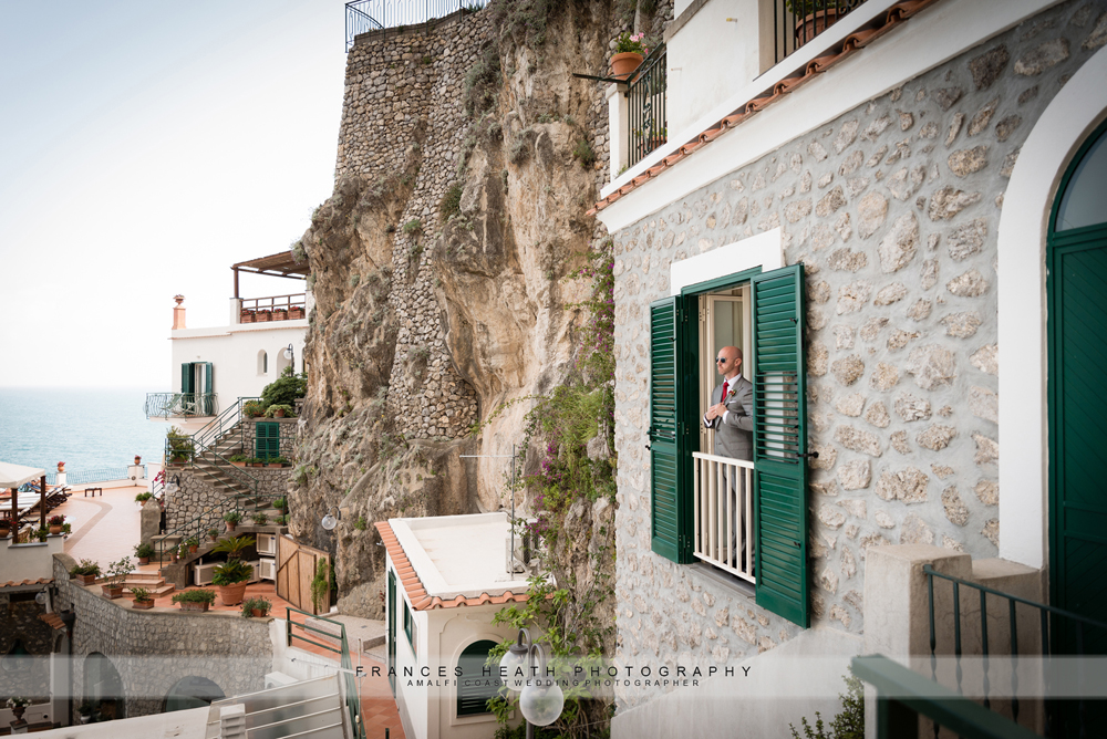 Groom looking at view from hotel on the Amalfi coast