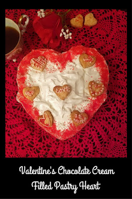 this is a chocolate heart cream pastry filled with chocolate pudding, whipped cream, espresso coffee, a rose and old vintage serving cutter. The photo has the Valentines day  heart shaped dessert  that will be served in a glass bowl  cut up