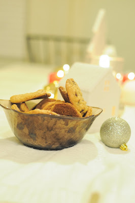 bowl of chocolate chip cookies and glowy candles at a holiday party