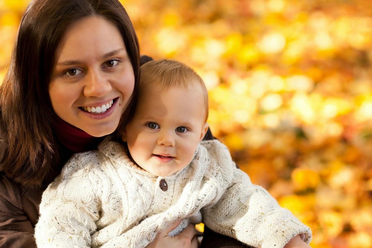 Mutter mit Baby im Herbstlaub