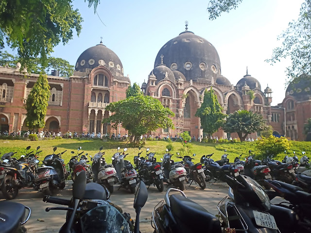 Red sandstone and black domed Arts Faculty building at MS University Baroda, with garden in front and two rows of parked motorcycles