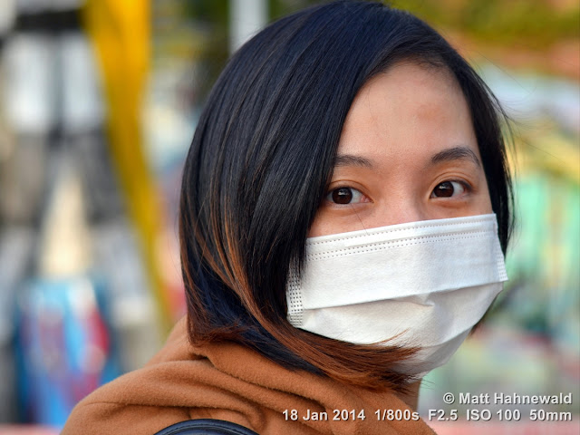 Matt Hahnewald; Facing the World; people; portrait; street portrait; headshot; Nikon DSLR D3100; Nikkor AF-S 50mm f/1.8G; Asia; Taiwan; Kaohsiung; Taiwanese woman; beautiful; charming; beautiful eyes; Oriental eyes; face mask; smiling eyes; travel; travel destination; tourism; world cultures; fashion; hygiene; epicanthic fold; rapport; eye contact