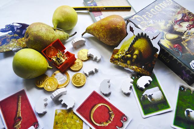 Fruta y monedas junto a las cartas de ovejas y coronas