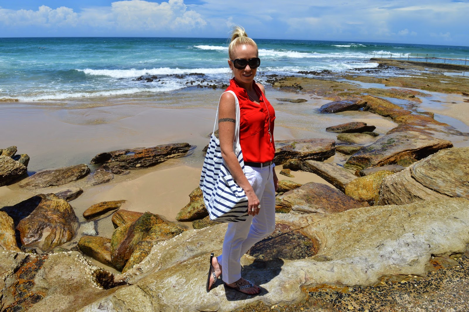 SFH in white pants and a red sleeveless top at Cronulla beach.