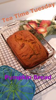 "Words read, ""tea Time Tuesday.  Pumpkin Bread"" in orange and bright purple over an image of a loaf of pumpkin bread in a glass bread pan.  Two colorful oven mits lay on the stove top beside it."