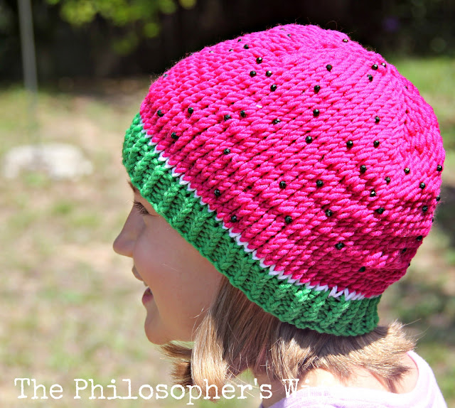 A smiling girl is wearing a knitted watermelon hat.