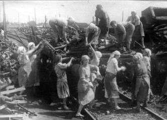"""Женская бригада завода """"Вторчермет"""" за погрузкой на железнодорожную платформу отсортированного металлолома из трофеев"""