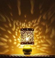 Gece yanan ve duvara desenli ışıklar yayan bir abajur