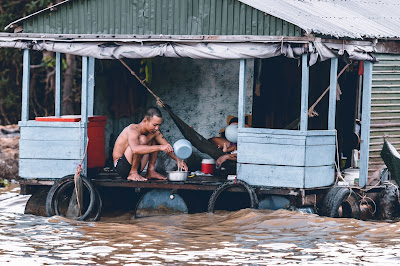 A man using dirty water in his house near a river