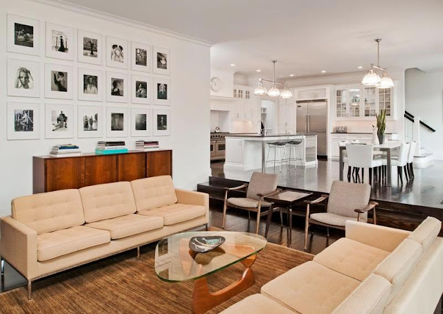 Den in a mansion with an open kitchen, dueling sofas and a Noguchi coffee table