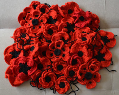 A pile of red and black crocheted poppies of different designs arranged in a circular 'hill' on the neutral-coloured sofa.
