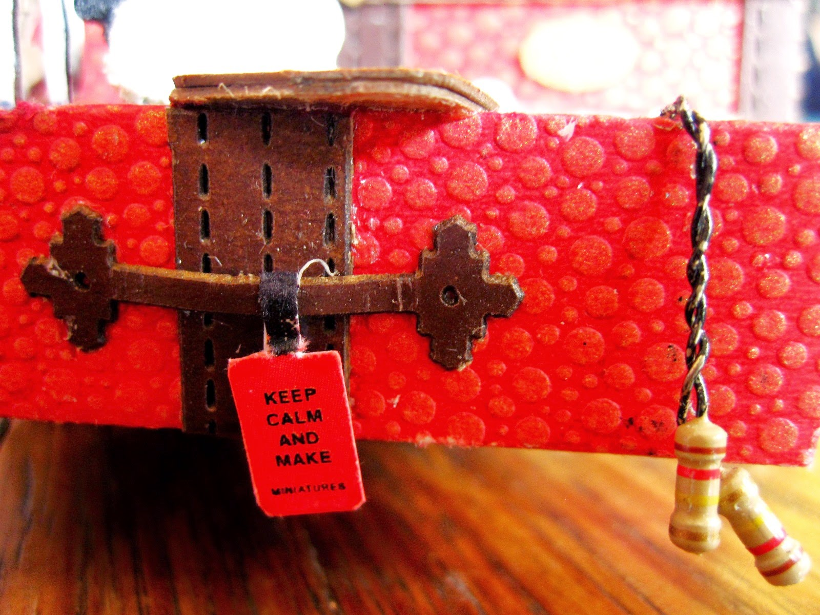 Miniature red trunk with skipping rope hanging over the edge and tag which reads 'Keep calm and make miniatures'