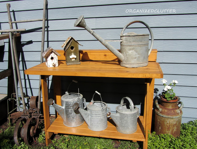 Potting Bench With Watering Cans and Vintage Farm Tools