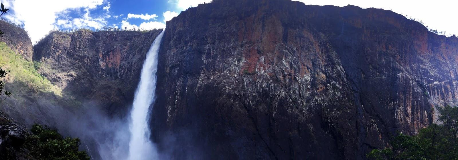 Wodospad Wallam Falls z dołu. Zdjęcie panoramiczne, pokazuje wysokie skarpy znajdujące się niemalże dookoła wodospadu