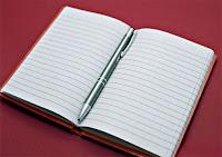 Ortasında kalem olan küçük, açık ve çizgili bir boş defter