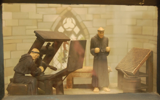 Front view through glass of diorama featuring monks printing the Bible on a printing press