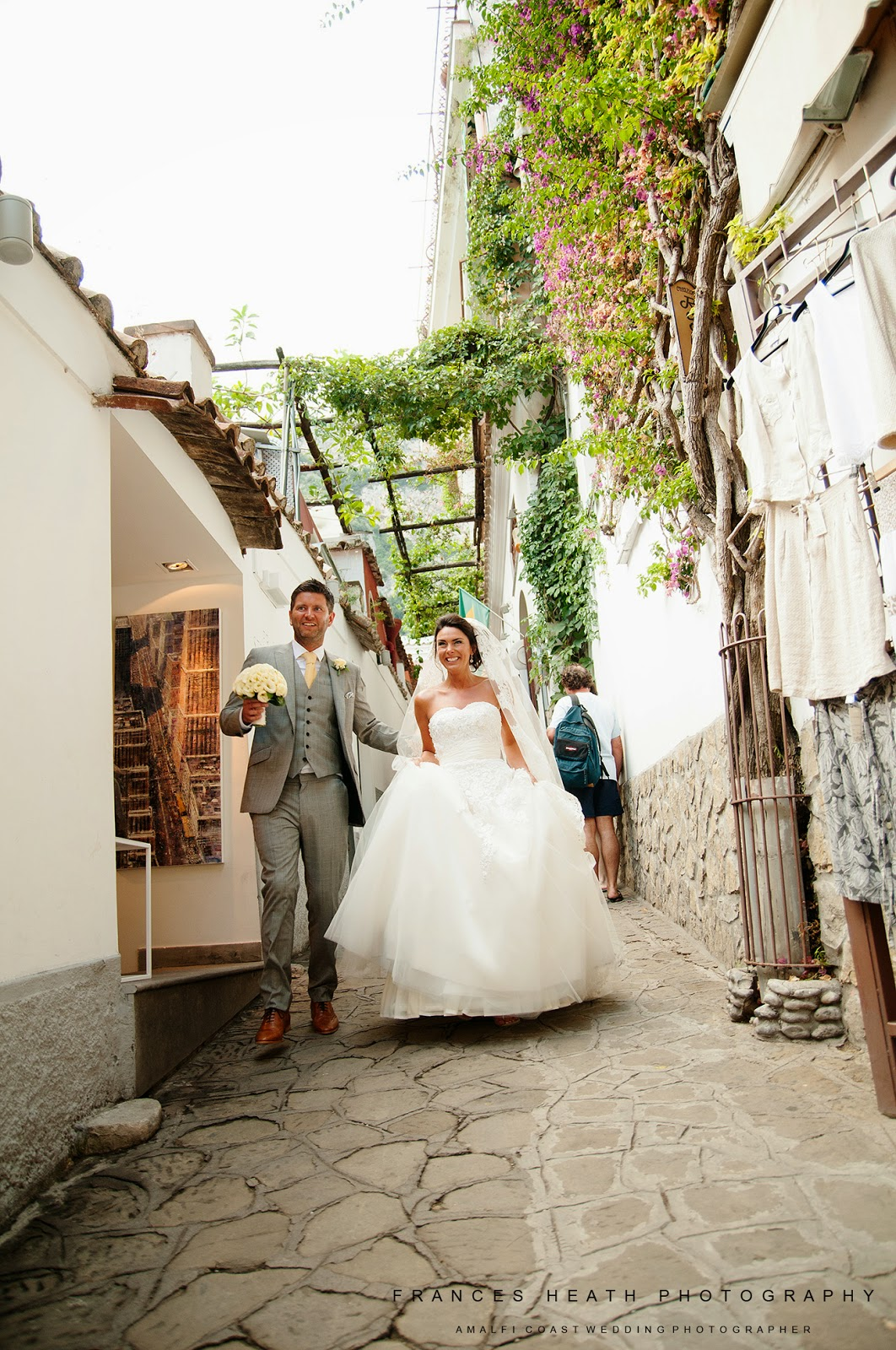 Bride and groom walking through street in Positano