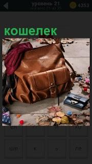 Большая сумка на земле и рядом лежит небольшой кошелек. на сумке сверху положена одежда