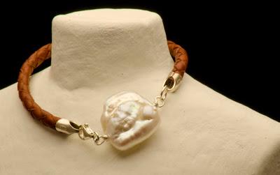 Pulsera de perla barroca, montada en cuero trenzado en color natural con pasadores y terminales en plata