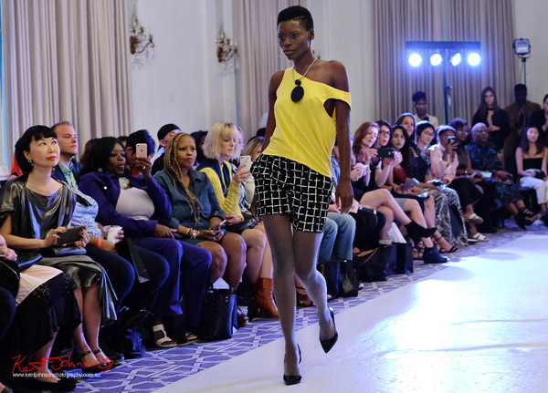 A model in yellow singlet, black check shorts, André Bryson - Guerrilla - NYFW. Photographed for Street Fashion Sydney by Kent Johnson.