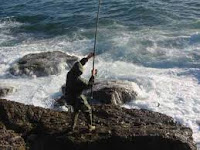 Foto de um pescador escorregando nas pedras de um arrecife