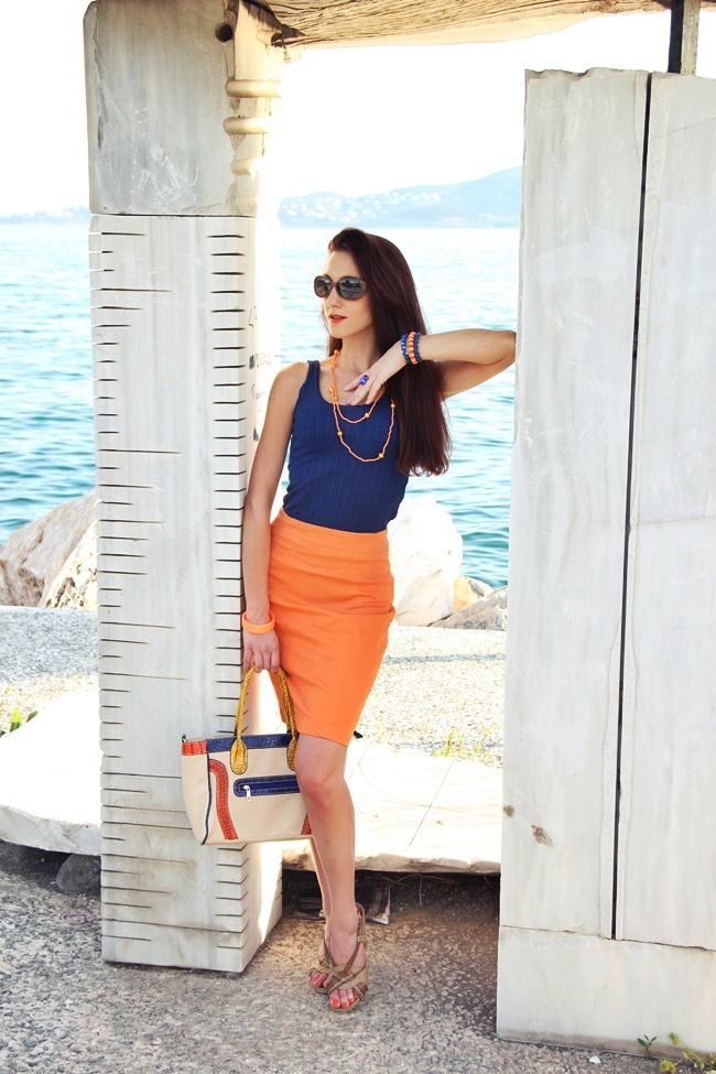 Orange pencil skirt and navy knitted top beige sandals and bag