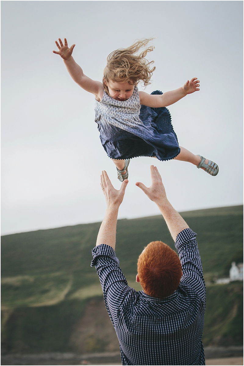 Father throwing young daughter in the air
