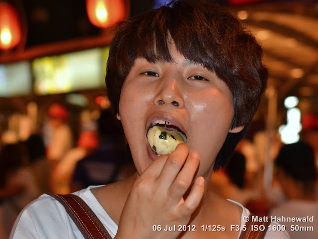 China, Beijing, Donghuamen night market, Chinese food delicacies, portrait, Chinese woman eating steamed dumplings, jiaozi