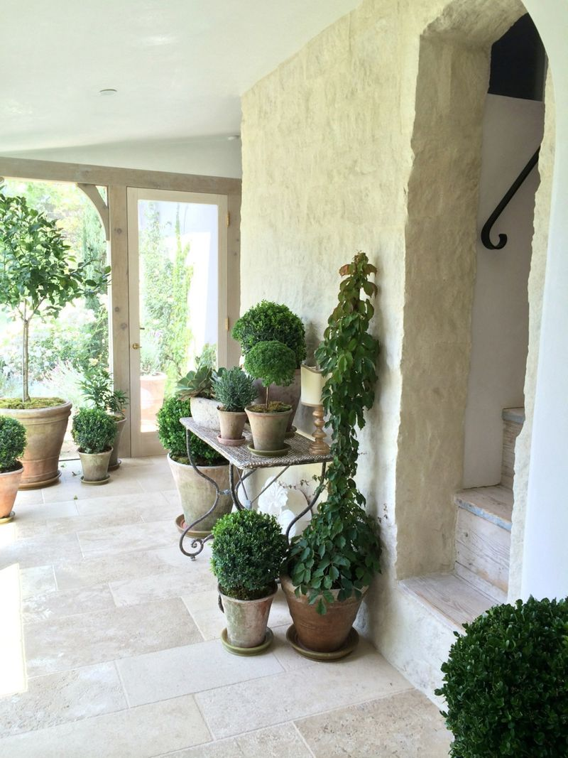 French inspired garden room with limestone flooring and potted plants at Patina Farm