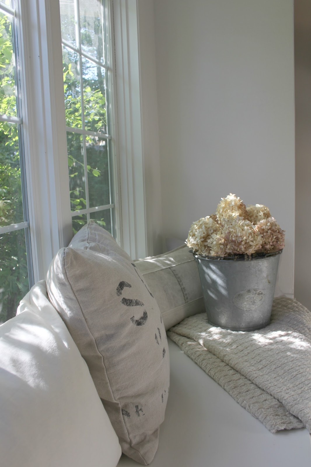 Window seat in breakfast room of kitchen. Belgian linen piillows and vintage galvanized pail holding dried hydrangea. Paint color is Bejamin Moore WHITE. Come explore How to Decorate a Room Without Breaking the Bank: Low Cost Design Reminders.