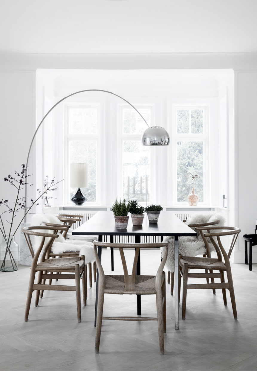 Dining table inside of a bright scandinavian interior in nordic villa with hans wegners chairs and black furniture and arco lamp