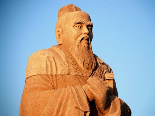 Estátua de Confúcio, mãos cruzadas sob um plácido céu de brigadeiro