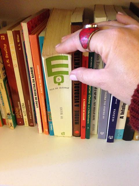 a escolher um livro da prateleira