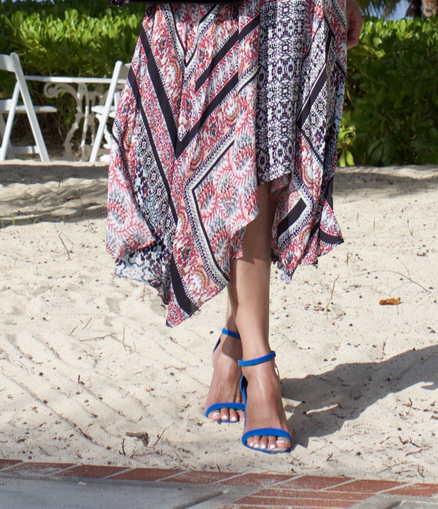Close-up of Parker dress with handkerchief hemline, standing in sand