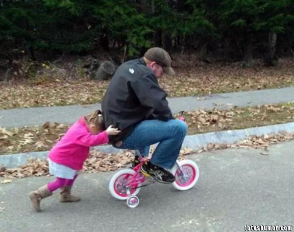 niñá empujando a su papa en un triciclo