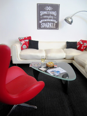 Modern one-tweltfh scale miniature hotel lobby in red, white and black. On the coffee table are a selection of postcards, a glass of wine and a travel magazine.