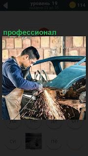 Профессионал шлифует бампер машины в мастерской в рабочей форме