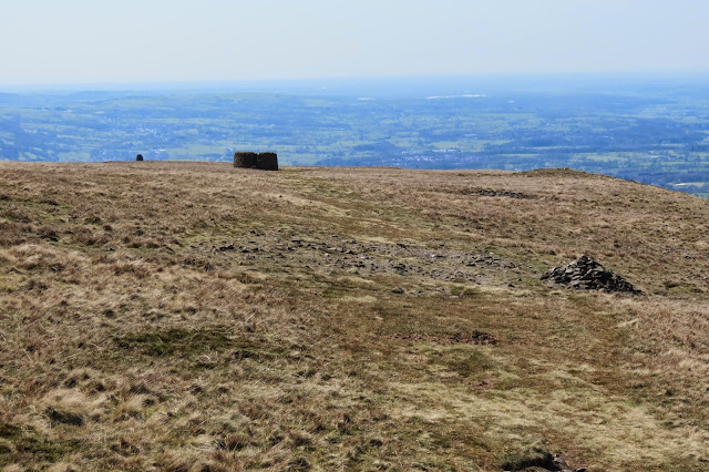 A view across the grassy expanse of Pendle Hill to the stone shelter and cairn ahead, with Lancashire farmland in the background.