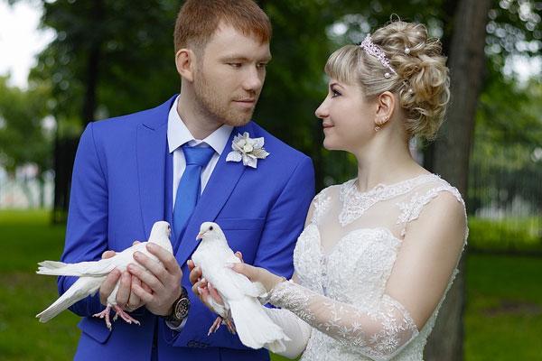 marido e mulher juntos segurando duas pombas