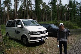 """Ein großer, weißer Bus mit der Aufschrift """"WDR"""", daneben ein blauer Mercedes."""