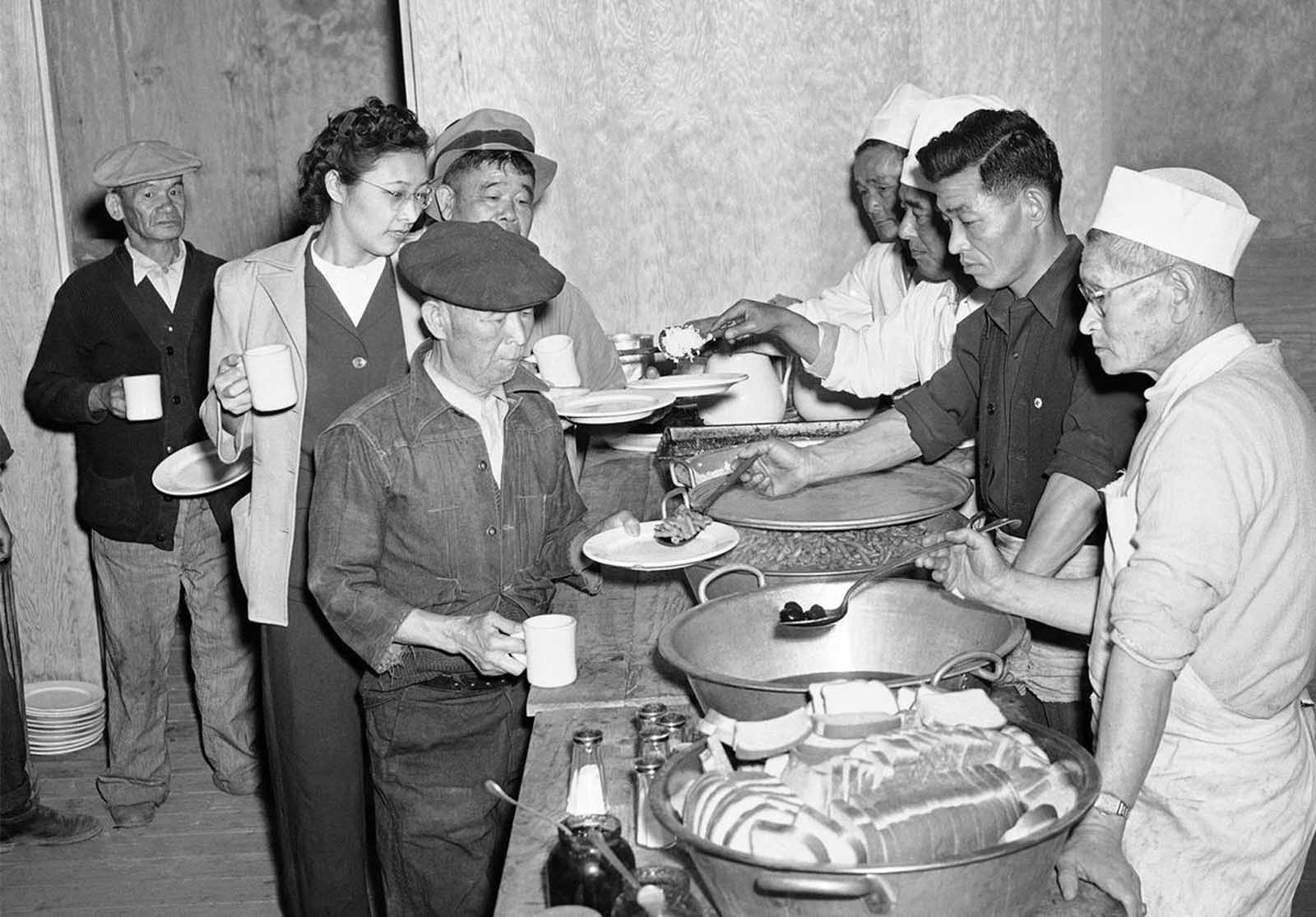 apanese Americans removed from their Los Angeles homes line up at Manzanar Relocation Center, in California, on March 23, 1942, for their first meal after arrival at the camp. Rice, Beans, Prunes, and bread were included in the menu.