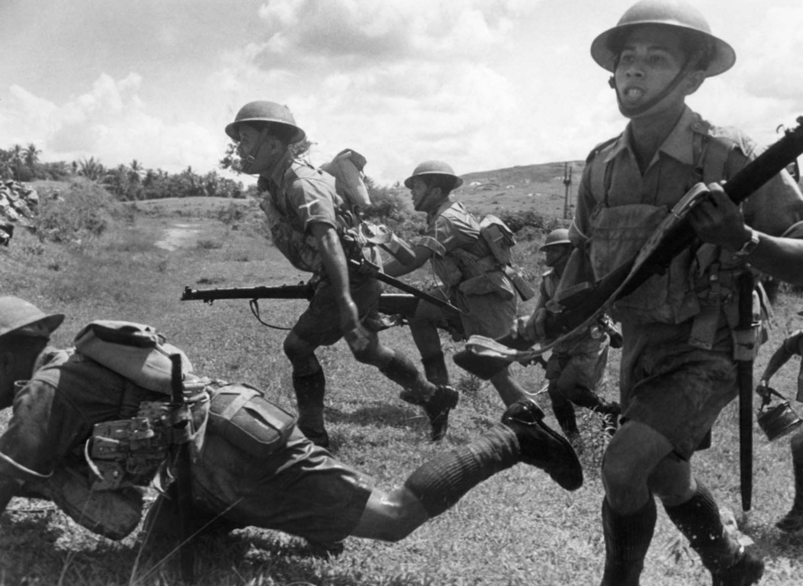 Malayan soldiers intent on defending their peninsula charge forward at a Malay battle zone on February 10, 1942, before the Japanese completed their occupation of the peninsula and pushed Britons back onto Singapore Island.