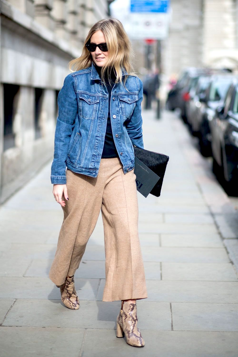 Effortless Denim Jacket Outfit Idea for Spring — Lucy Williams street style look in a black turtleneck top, tan cropped pants, snake-print ankle boots