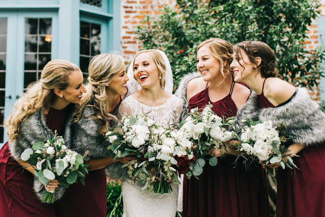 bride with bridesmaids in red dresses with faux fur coverups