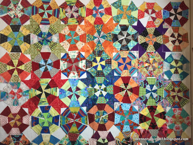 Multicolored fabrics create a cheerful, bright kaleidoscope quilt.